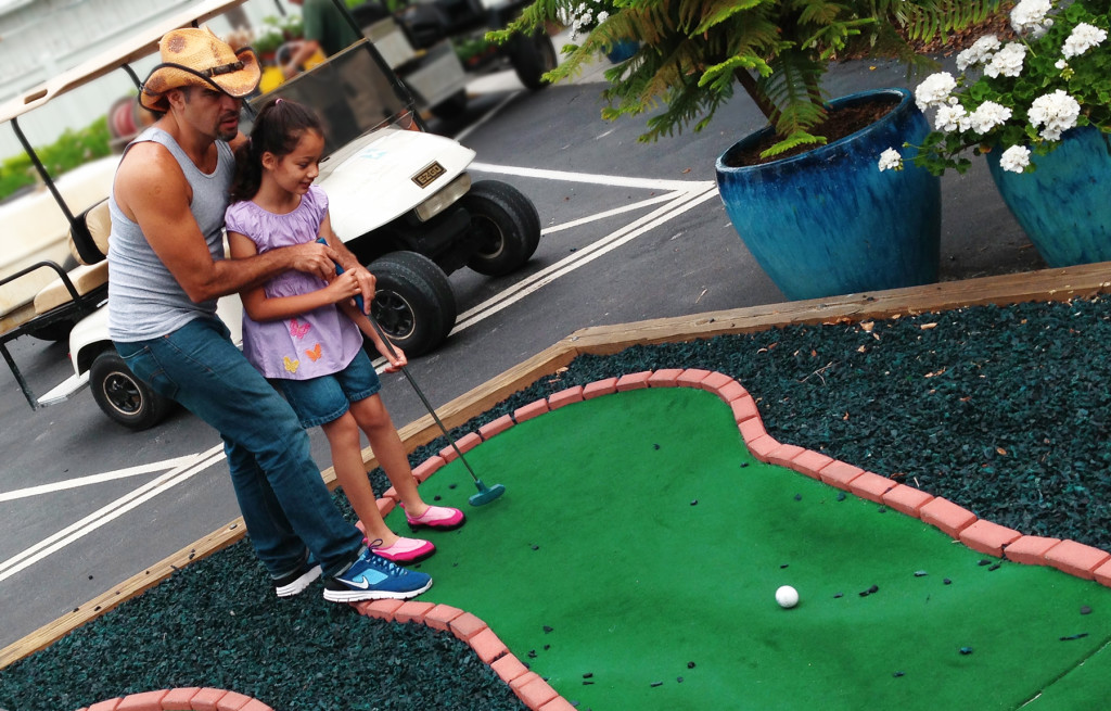 My daughter learning to play mini golf with Daddy. Photo: Paula Bendfeldt-Diaz. All Rights Reserved.