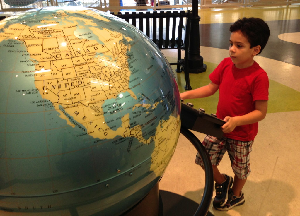 boy looking at 3D map of the world