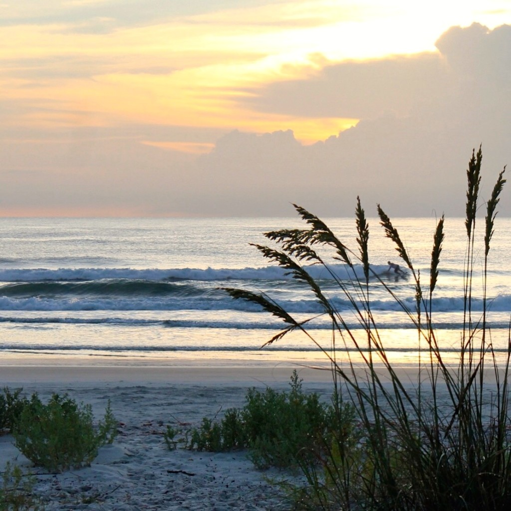 Sunrise at New Smyrna Beach with surfer in the background.