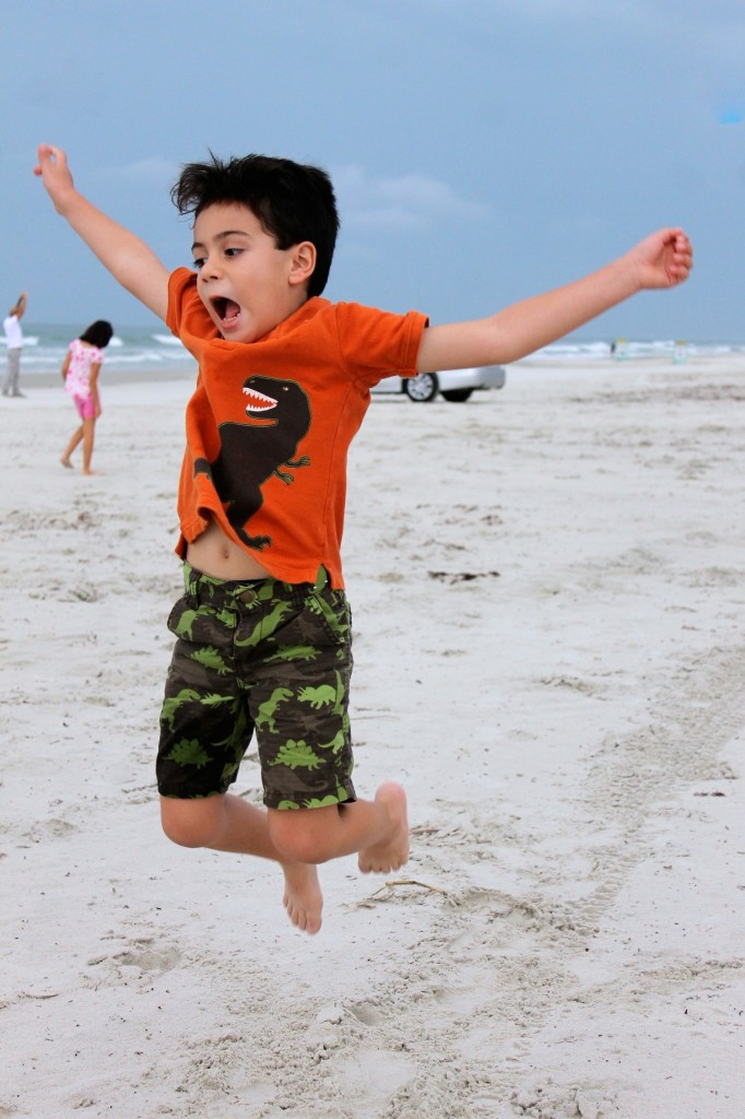 New Smyrna beach, boy jumping for joy at the beach with car in the background.